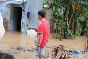 马尼拉一名男子注视着自己被淹的房屋