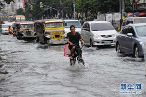 菲律宾男子在积水的道路上骑车前行