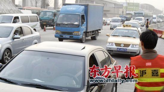 沪嘉高速公路主线收费站,工作人员在道口收取区间通行卡,以加快通行速度。