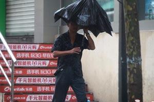 路人顶着被风吹坏的伞艰难前行