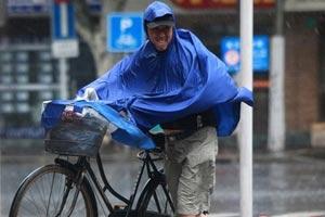 骑车人只好在风雨中推行自行车