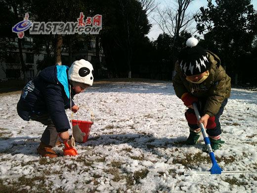 孩子们在难得一见的雪地上玩起铲雪的游戏。