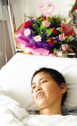 """图片说明:曾被誉为""""最美钟点工""""的何益红仍躺在病床上"""