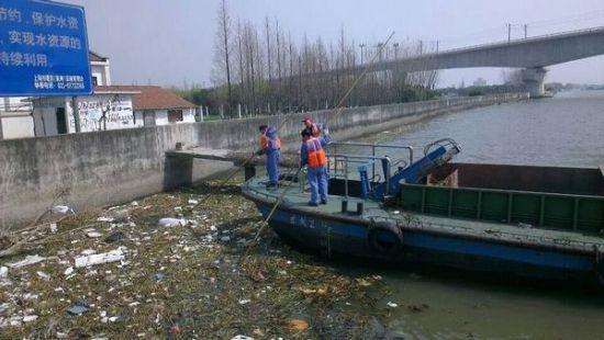 工作人员在打捞水中的污染物。 网友供图