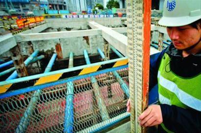 轨道交通汉中路枢纽13号线车站施工现场,施工人员正在测量。 晨报记者 竺钢