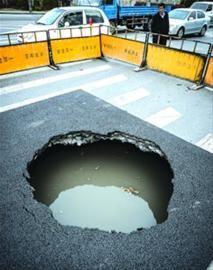 □昨日,文翔路塌陷的圆形大坑内充满积水。 晨报记者 肖允