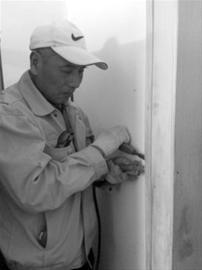 灭蚁师试图撬开门框往墙深处喷洒药水