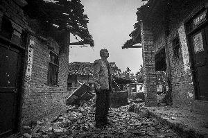 21日,雅安市芦山县龙门乡,一位老人抬头看着已经被地震所损毁的房屋。早报记者 杨深来 图