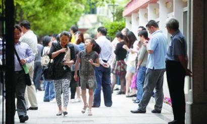 """每年的 """"小升初""""报名期间,学校门口都会站满等待的家长。/晨报记者 吴磊"""