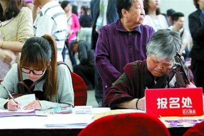 相亲会现场,一名女青年和一名家长正在填写报名表。 蒋迪雯 摄