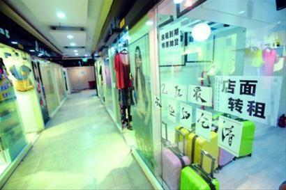 """□紧邻静安寺地铁站的伊美时尚广场内,一些店铺贴出 """"转让旺铺""""告示。/晨报记者 杨眉"""
