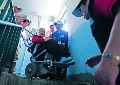 114岁老人李素清在志愿者的帮助下,利用爬楼机下楼去小区逛逛。 晨报记者 殷立勤