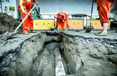市政人员处置延安西路定西路口的坑。 肖允 摄