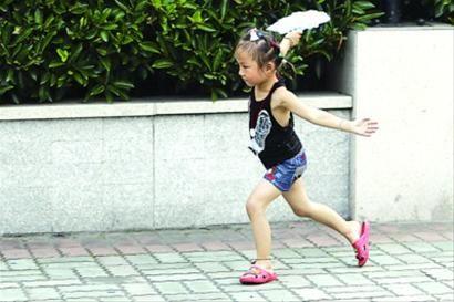 □昨日天气闷热,一名小女孩穿着凉快的夏服在路边奔跑着。 /晨报记者 殷立勤