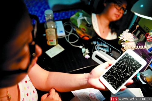 苏小姐的HTC手机在充电过夜后,屏幕爆裂。本报记者 丁嘉 摄