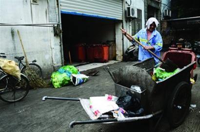 周立怀将一车垃圾铲入垃圾箱内 /晨报记者赵磊