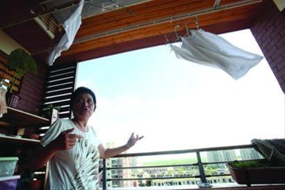 关永霞在临港新城10楼的家,开窗即有海风,不用开空调就很凉爽。/晨报记者 杨眉