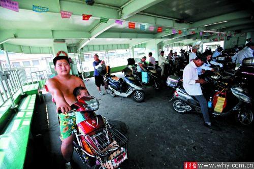 南陆线过江轮渡上闷热不堪,乘客打起赤膊。青年报记者 丁嘉 摄