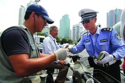 交警在给遵守交通秩序的人们奖励景点门票。 陈暐摄