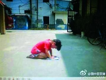 """女孩跪在水泥地上写作业 /网友""""圈中豆豆猪"""""""