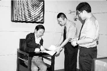 孙联生接受检察官讯问,在讯问笔录上签字。龚佩琳摄