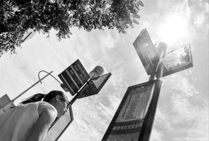 □由于没有遮阳棚,乘客不得不顶着烈日等待公交车。/晨报记者 肖允