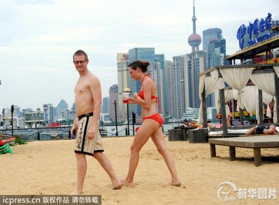 不少中外游客乘着双休日,在这里晒日光浴,泡微型泳池,享受水中的凉爽。