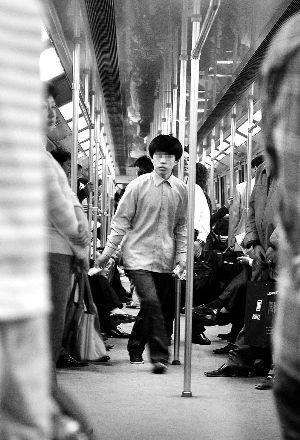 一名男子正在轨交2号线车厢内向乘客发小广告。早报资料