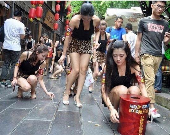 这些身穿豹纹短裙的美女们有的默默捡拾过往路人