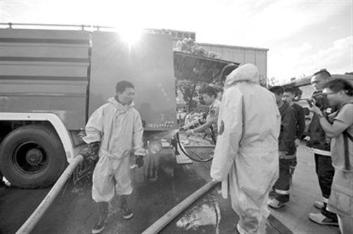 消防队员用高压水枪为刚走出事发现场的救援人员冲洗衣物,稀释可能附着的有害物质。 本报记者 叶辰亮摄