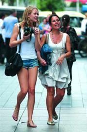 □昨日最高温仍接近30℃,身着夏装游客漫步在南京东路步行街。 /新华社