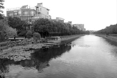 城市岸泊外的青龙江,亲水平台(左侧)明显低于对岸防汛墙,通往小区河口仅有几块石头。 /晨报记者 杨育才