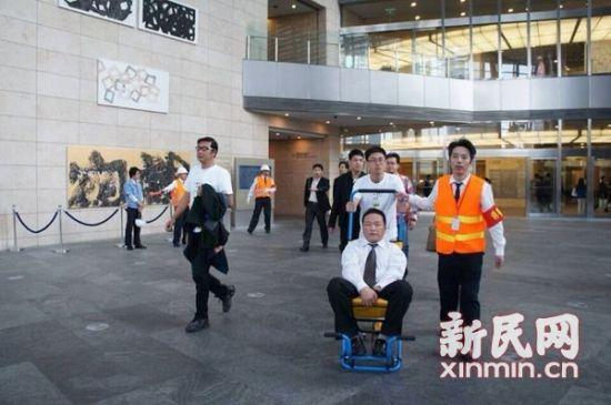 图说:10月24日,上海环球金融中心举行防灾综合训练,首次试用残疾人专用特殊轮椅。上海环球金融中心供图