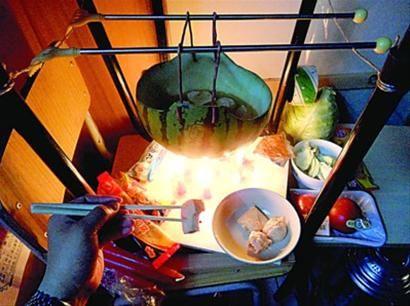 □两张椅子被面对面叠在一起,穿了两根线的西瓜皮就悬空在椅脚中间,下面有蜡烛加热,这就是西瓜火锅。