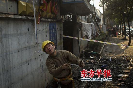 昨日,逸仙路1901号,一位电力抢修人员正在查看被烧断的电缆。早报记者 杨深来 图