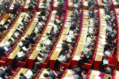□人大代表在会上翻阅政府工作报告 /晨报记者 竺钢