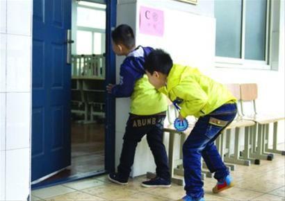 """等候面试的小朋友在教室外""""打探虚实""""。目前不少城市择校热都集中在民办小学 /新华社"""