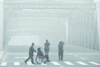 昨日下午2时,游客在外白渡桥上留影,大雾中的桥身若隐若现。 /张海峰