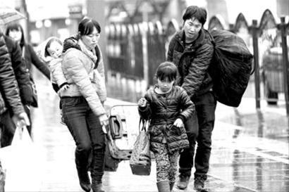 昨天,乘客冒雨走出上海火车站。明天局部地区或将有雨夹雪,阴冷潮湿的天气将给返沪旅客带来不便。 蒋迪雯
