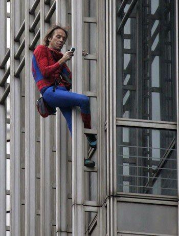 阿兰·罗伯特在攀登金茂时看手机