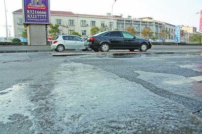 图为地下水管破裂导致路面结冰成溜冰场。
