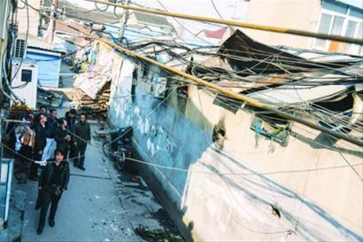 起火店铺屋顶被熏得焦黑,部分铁皮破裂翘起。晨报记者 肖允