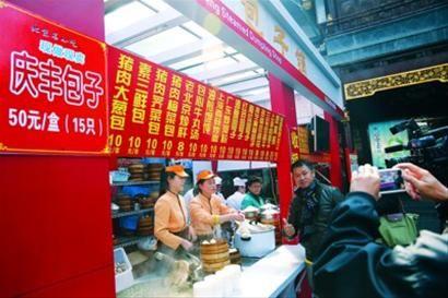 □庆丰包子来到上海,许多市民不仅慕名前来购买,而且还当起了粉丝,与庆丰包子铺合影。/晨报记者 殷立勤