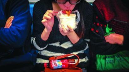 □尽管《守则》明确要求轨交车厢内不能进食,但仍有不少乘客在乘客在坐车时吃东西。 /晨报记者 肖允