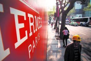 昨日,上海市淮海中路,市民经过一家即将在年底开业的奢侈品旗舰店外墙。早报记者 寇聪 图