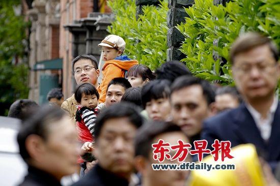 昨天早晨,近百位家长在延安中路幼儿园门口排起长队等待为孩子报名。早报记者 张栋 图