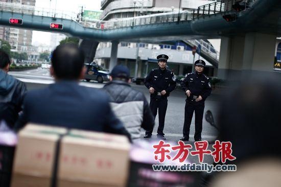 昨日,江苏路派出所的两位佩枪民警在江苏路延安西路交叉路口巡逻。 早报记者 杨一 图