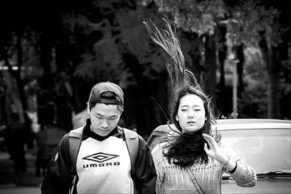 """□昨天天气几度""""变脸"""",大风让行人手忙脚乱。 /晨报记者 肖允"""