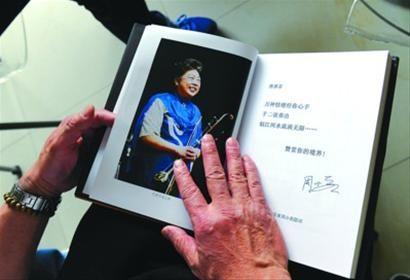 □昨天,丈夫刘振学深情抚摸着《闵惠芬二胡艺术集成》/晨报记者何雯亚