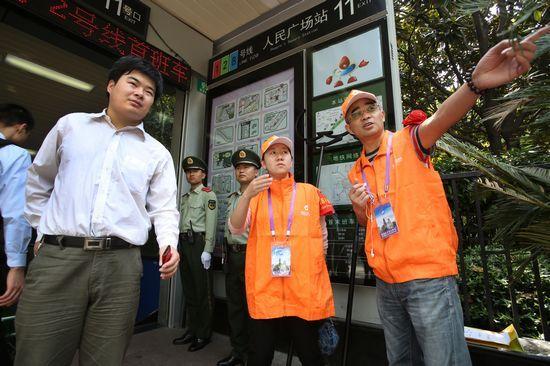 两名来自学校的平安志愿者穿上黄马甲、戴上红袖章,在地铁人民广场站出入口执勤。东方IC 图
